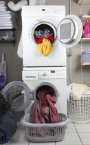 This is a photo of a stacked washer and dryer with their doors open and clothes spilling out.